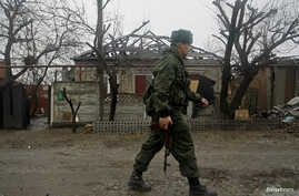 FILE - A member of the self-proclaimed Donetsk People's Republic (DNR) walks past a house damaged by shelling in Donetsk, Ukraine.