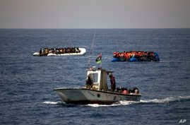 FILE - A Libyan Coast Guard ship sails past two rubber boats packed with migrants and refugees in the Mediterranean Sea, about 18 miles north of Sabratha, Libya, June 15, 2017.