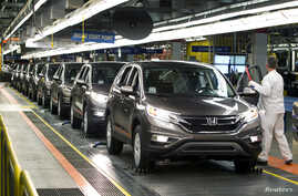 FILE - Production Associates inspect cars moving along the assembly line at a Honda manufacturing plant in Alliston, Ontario, March 30, 2015.
