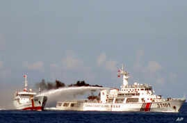 FILE - Image released by Vietnam Coast Guard, a Chinese coast guard vessel, right, fires water cannon at a Vietnamese vessel off the coast of Vietnam.