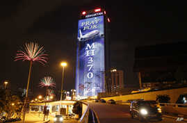 """An office building is illuminated with lights displaying """"Pray for MH370"""" in Kuala Lumpur, Malaysia, March 24, 2014."""