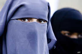 FILE - Unidentified women are seen wearing a niqab during a demonstration outside the Dutch parliament against a proposed ban on the burqa, in The Hague, Netherlands.