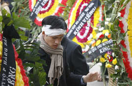 FILE - Vietnamese dissident Nguyen Tien Trung stands between wreaths during a funeral for Hoang Minh Chinh in Ho Chi Minh City, February 16, 2008.