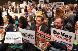 Sergio Martinez, center, a teacher at Sparks Elementary School in La Puente, Calif., joins hundreds of others as California educators voice their opposition to President Donald Trump's nomination of Besty DeVos as Secretary of Education, in Los Angel