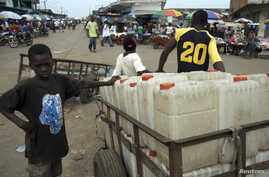 FILE - A boy sells jerrycans at a market area in the Liberian capital of Monrovia.