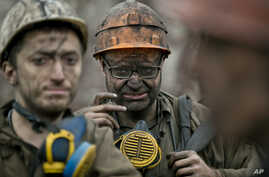 Ukrainian coal miners wait for a bus after exiting the underground of the Zasyadko mine in Donetsk, Ukraine, March 4, 2015.
