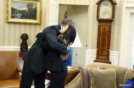 President Barack Obama hugs Dallas nurse Nina Pham as her mother Diane looks on, Oval Office, Washington, Oct. 24, 2014.