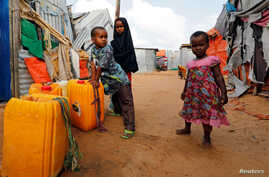Somali children stand outside their makeshift shelter at a camp for the internally displaced people outside Mogadishu, Somalia August 28, 2018 .