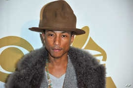 """Pharrell Williams arrives at """"The Night That Changed America: a Grammy Salute to the Beatles,"""" Jan. 27, 2014, in Los Angeles"""