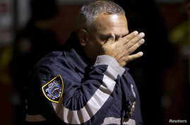 A police officer wipes tears from his face as he walks away from the site where two New York City police officers were shot dead in the Brooklyn borough of New York, Dec. 20, 2014.