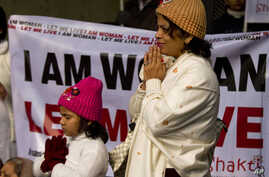 An Indian woman and her daughter pray as they take part in a silent protest to mourn the death of a gang rape victim in New Delhi, India, Tuesday, Jan. 1, 2013.
