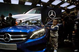 Chinese regulators have launched a series of anti-monopoly investigations of foreign automakers. In this photo taken Sunday, April 20, 2014, a child touches the latest model from Mercedes at an auto show in Beijing.