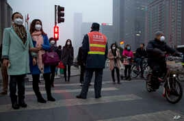 Pedestrians wearing mask against heavy pollution wait to cross a traffic junction in Beijing, China, March 16, 2015.