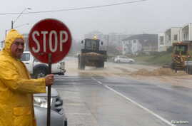Loaders move tons of sand pushed by strong winds and rain onto a coastal road in Sydney's beachside suburb of Cronulla, April 21, 2015.