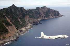 (File) This photo from Oct. 13, 2011, shows Japanese Maritime Self-Defense Force plane flying over the disputed islets known as the Senkaku islands in Japan and Diaoyu islands in China, in the East China Sea.