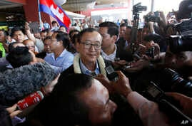 Sam Rainsy, center, leader of the opposition Cambodia National Rescue Party (CNRP), talks to journalists upon his arrival at Phnom Penh International Airport in Phnom Penh, Cambodia, Aug. 16, 2015.