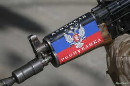 """A pro-Russian armed man stands guard at a barricade in Slaviansk, Ukraine. The sticker on his rifle reads """"Republic of Donetsk."""" April 28, 2014."""