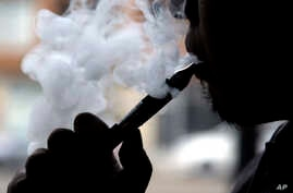 Daryl Cura demonstrates smoking an e-cigarette at Vape store in Chicago, April 23, 2014.
