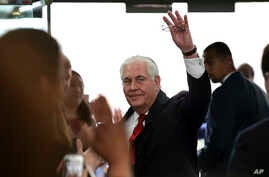 Outgoing Secretary of State Rex Tillerson waves goodbye as he walks out of the doors of the State Department in Washington, March 22, 2018, after speaking to employees upon his departure.