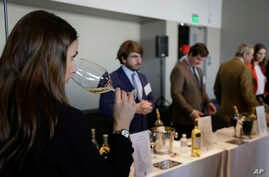 A woman tastes 2015 vintage wine from Barsac Sauternes during the Union des Grand Crus of Bordeaux tasting event  January 25, 2018, in San Francisco.
