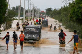 Residents wade through raging floodwaters brought about by Typhoon Koppu at Zaragosa township, Nueva Ecija province, north of Manila, Philippines, Oct. 19, 2015.