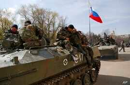 Combat vehicles with a Russian flag on one of them and gunmen on top are parked in downtown of Slovyansk, April 16, 2014.