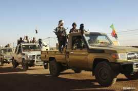 Soldiers from the Tuareg rebel group MNLA drive in a convoy of pickup trucks in the northeastern town of Kidal, Mali, February 4, 2013.