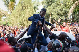 Ugandan pop star turned opposition MP, Robert Kyagulanyi, is helped by his supporters as he delivers a speech outside his home in Kampala, Uganda, after returning from the United States on Sept. 20, 2018.
