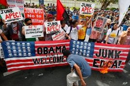 Protesters burn mock American flags during a rally outside of the US Embassy to protest alleged US military's involvement in the row between the Philippines and China on the disputed islands in the South China Sea, Thursday, in Manila, Philippines, N