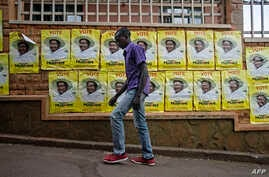 A man walks past election posters for incumbent President Yoweri Museveni in Kampala on Feb. 11, 2016.