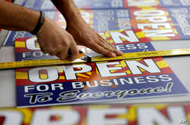 """Tom Cushing, a production expert at Fast Signs, cuts down a sheet of anti-Senate Bill 1062 signs that read """"Open For Business To Everyone,"""" in Phoenix, Arizona, Feb.26, 2014."""