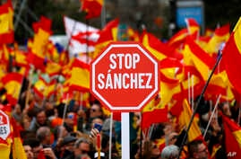 Demonstrators hold banners and Spanish flags during a protest in Madrid, Spain, Feb.10, 2019.