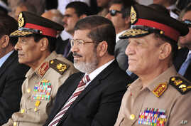 In this Thursday, July 5, 2012 file image released by the Egyptian President, Egyptian Field Marshal Gen. Hussein Tantawi, left, new President Mohammed Morsi, center, and Armed Forces Chief of Staff Sami Anan, right, attend a medal ceremony, at a mil