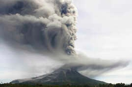 Mount Sinabung spews volcanic material as it erupts as seen from Tiga Pancur, North Sumatra, Indonesia, Monday, Nov. 18, 2013.