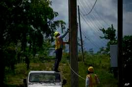 Workers of the electric repair brigade remove old cables from a post in San German, Puerto Rico, May 30, 2018.