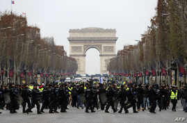 French riot police take position in front of protesters wearing yellow vests (gilets jaunes) demonstrating against rising costs of living they blame on high taxes on the Champs-Elysees in Paris, Dec. 15, 2018.