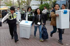 South Korean National Election Commission officials and police officers carry boxes containing ballots for parliamentary election as they arrive at a ballot counting office in Seoul, South Korea, April 13, 2016.