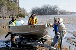 Tom Wilke, center, his son Chad, right, and Nick Kenny, load a boat out of the swollen waters of the North Fork of the Elkhorn River after checking on the Witke's flooded property, in Norfolk, Neb., Friday, March 15, 2019.