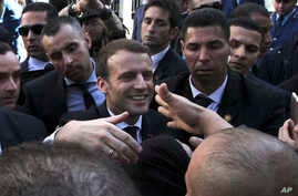 French President Emmanuel Macron shakes hands as he meets residents in Algiers, Wednesday, Dec.6, 2017.