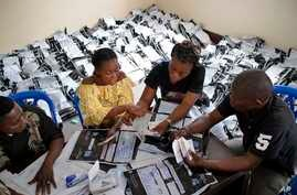 FILE - Congolese independent electoral commission (CENI) officials count the presidential ballots from over 900 polling stations at a local results compilation center in Kinshasa, Jan. 4, 2019.