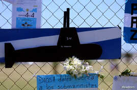 """A bouquet of flowers and banners in support of the 44 crew members of the missing ARA San Juan submarine are placed on a fence outside an Argentine naval base in Mar del Plata, Argentina, Nov. 25, 2017. The banner below reads """"God, give strength to t"""
