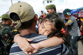 A girl falls asleep on her father's shoulders as they wait with other survivors to be airlifted to Manila, in the aftermath of super typhoon Haiyan at the Tacloban airport, Nov. 14, 2013.