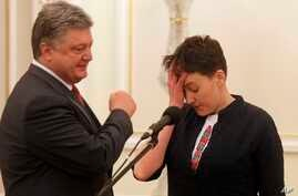 Ukrainian President Petro Poroshenko, left, looks at Ukrainian jailed pilot Nadezhda Savchenko  during their meting  in the Presidential Office in Kyiv, Ukraine, May 25, 2016.