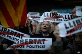 Demonstrators gather during a protest calling for the release of Catalan jailed politicians, in Barcelona, Spain, Nov. 11, 2017.  Eight members of the now-defunct Catalan government remain jailed in an alleged rebellion case. The banners read in Cata