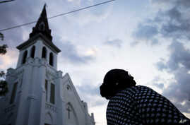 Doris Simmons, of Charleston, S.C. stands next to Emanuel AME Church, the scene of last week's mass shooting, as the sun rises, June 26, 2015, in Charleston.