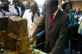 "Zimbabwe's President Robert Mugabe cuts his birthday cake as he marks his 93rd birthday at his offices in Harare, Tuesday, Feb. 21, 2017. Mugabe described his wife Grace, an increasingly political figure, as ""fireworks"" in an interview marking his 93..."
