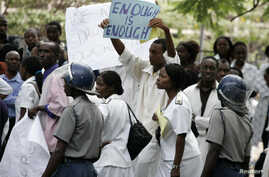 FILE - Zimbabwean riot policemen stand in front of doctors and nurses who are demonstrating over the deteriorating health system, outside Parirenyatwa group of hospitals in Harare, Nov. 18, 2008.