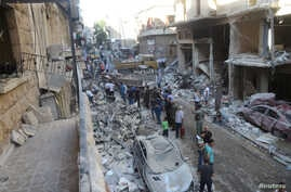 People inspect the damage at a site after it was hit by shelling carried out by rebels at Syrian government-held areas of Aleppo, Syria, in this handout picture provided by SANA, July 11, 2016.