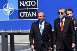 FILE - Turkish President Recep Tayyip Erdogan, right, and Foreign Minister Mevlut Cavusoglu arrive for a NATO summit in Brussels< Belgium, May 25, 2017.