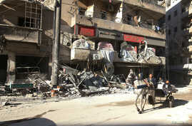 People ride a cart pulled by a horse near the damaged al-Hakeem hospital, in the rebel-held besieged area of Aleppo, Syria, Nov. 19, 2016.